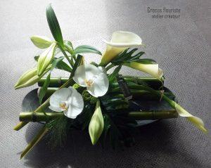 Composition de fleurs blanches sur un radeau de bambous verts